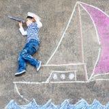 Muchacho del niño que se divierte con el dibujo de la imagen de la nave con tiza Imagenes de archivo
