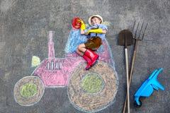 Muchacho del niño que se divierte con la imagen de las tizas del tractor Foto de archivo
