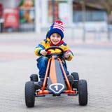 Muchacho del niño que se divierte en el coche de carreras del juguete al aire libre Foto de archivo libre de regalías