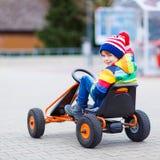Muchacho del niño que se divierte en el coche de carreras del juguete al aire libre Foto de archivo