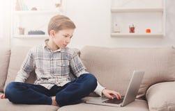 Muchacho del niño que usa el ordenador portátil en el sofá en casa Foto de archivo libre de regalías