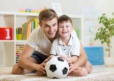 Muchacho del niño con fútbol del juego del papá en casa Imágenes de archivo libres de regalías