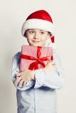 Muchacho del niño de la Navidad en Santa Hat y regalo Imagen de archivo libre de regalías