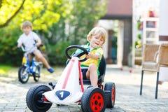 Muchacho del niño que conduce el coche del pedal en jardín del verano Fotos de archivo
