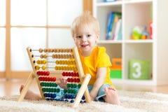 Muchacho del niño que juega con el juguete contrario en casa Imagen de archivo