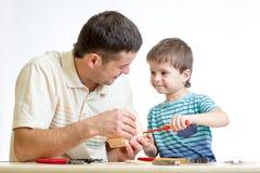 Muchacho del papá y del niño que trabaja junto Fotografía de archivo libre de regalías