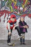 Muchacho del patinador con una niña Imagen de archivo
