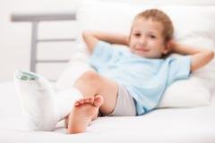 Muchacho del pequeño niño con el vendaje del yeso en fractura o el Br del talón de la pierna Imagen de archivo libre de regalías