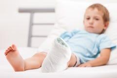Muchacho del pequeño niño con el vendaje del yeso en fractura o el Br del talón de la pierna Imágenes de archivo libres de regalías