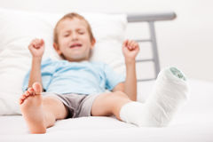 Muchacho del pequeño niño con el vendaje del yeso en fractura o el Br del talón de la pierna Fotografía de archivo libre de regalías