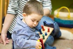 Muchacho del pequeño niño que juega en guardería en la clase de Montessori imagenes de archivo