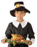Muchacho del peregrino que sirve el banquete de la acción de gracias Foto de archivo libre de regalías