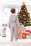 Muchacho del pijama con el juguete en el árbol de navidad imagenes de archivo