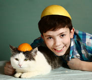 Muchacho del preadolescente con el gato masculino en casquillo anaranjado divertido Imágenes de archivo libres de regalías