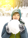 Muchacho del preadolescente con la bola de la nieve en parque del invierno Imagenes de archivo