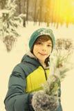 Muchacho del preadolescente con la bola de la nieve en parque del invierno Fotografía de archivo