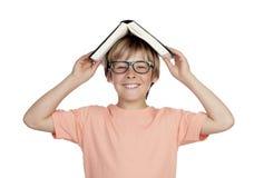 Muchacho del preadolescente con un libro y los vidrios Imágenes de archivo libres de regalías