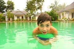 Muchacho del preadolescente en piscina del aire abierto con la bola Imágenes de archivo libres de regalías