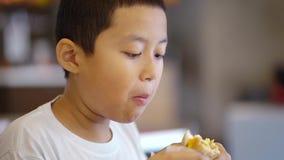 Muchacho del preadolescente que goza de un cheeseburger sabroso almacen de metraje de vídeo