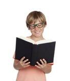 Muchacho del preadolescente que lee un libro con los vidrios Fotos de archivo libres de regalías