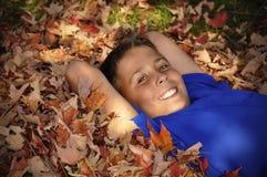 Muchacho del preadolescente que pone en hojas de otoño Fotografía de archivo libre de regalías