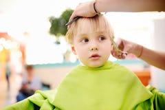 Muchacho del preescolar que consigue corte de pelo Imagen de archivo