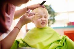 Muchacho del preescolar que consigue corte de pelo Imagen de archivo libre de regalías
