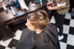 Muchacho del strechot del parihopher de la barbería del peluquero pequeño que se sienta en una silla Fotos de archivo