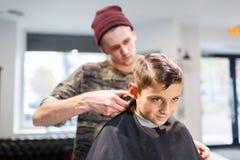 Muchacho del strechot del parihopher de la barbería del peluquero pequeño que se sienta en una silla Foto de archivo
