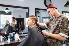 Muchacho del strechot del parihopher de la barbería del peluquero pequeño que se sienta en una silla Fotos de archivo libres de regalías