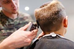 Muchacho del strechot del parihopher de la barbería del peluquero pequeño que se sienta en una silla Fotografía de archivo libre de regalías