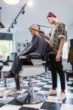 Muchacho del strechot del parihopher de la barbería del peluquero pequeño que se sienta en una silla Imagen de archivo libre de regalías