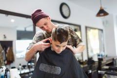 Muchacho del strechot del parihopher de la barbería del peluquero pequeño que se sienta en una silla Imagenes de archivo