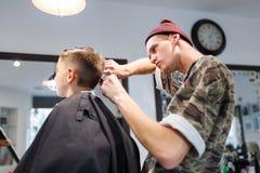 Muchacho del strechot del parihopher de la barbería del peluquero pequeño que se sienta en una silla Foto de archivo libre de regalías
