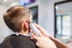 Muchacho del strechot del parihopher de la barbería del peluquero pequeño que se sienta en una silla Imagen de archivo