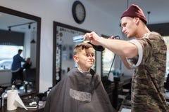 Muchacho del strechot del parihopher de la barbería del peluquero pequeño que se sienta en una silla Imágenes de archivo libres de regalías