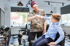 Muchacho del strechot del parihopher de la barbería del peluquero pequeño que se sienta en una silla Fotografía de archivo