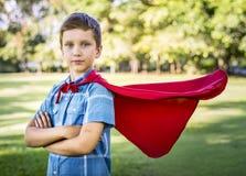 Muchacho del super héroe en el parque Fotos de archivo