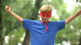 Muchacho del super héroe que muestra los músculos, juego como psicoterapia para la confianza del niño almacen de video