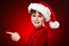 Muchacho del tiempo de la Navidad que señala en algo Fotografía de archivo