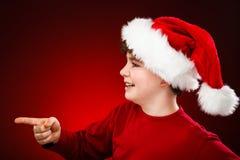 Muchacho del tiempo de la Navidad que señala en algo Fotos de archivo