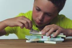 Muchacho del tween que se sienta en la tabla con los billetes de dólar Imagen de archivo libre de regalías
