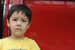 Muchacho delante de la pared roja Foto de archivo