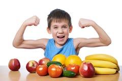 Muchacho deportivo sano con las frutas y verduras aisladas imagenes de archivo