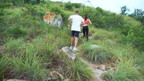 Muchacho deportivo y muchacha que corren en pista de la montaña La mujer y el hombre se resuelven en naturaleza almacen de video