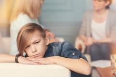 Muchacho deprimido del adolescente que se sienta en la oficina de un psicólogo profesional Foto de archivo