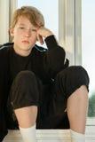 Muchacho deprimido que lleva el traje de sudor negro por las ventanas Imagenes de archivo