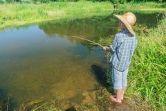 Muchacho descalzo de la pesca que pesca con caña en transparente Imagen de archivo