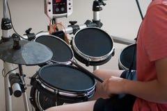 Muchacho desconocido en la camiseta rosada que practica los tambores electrónicos foto de archivo