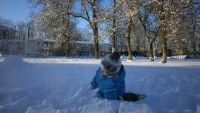 Muchacho despreocupado que juega en nieve Juego de las vacaciones de invierno de los niños en la cámara lenta Juego de la nieve d